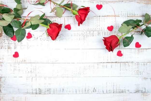 Rosas vermelhas com corações em um fundo branco de madeira, plana leigos, para texto. dia dos namorados