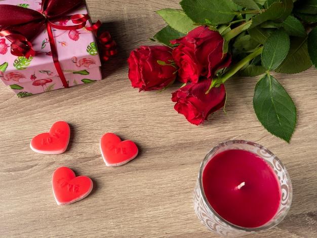 Rosas vermelhas com corações vermelhos de vela vermelha e presente rosa na mesa