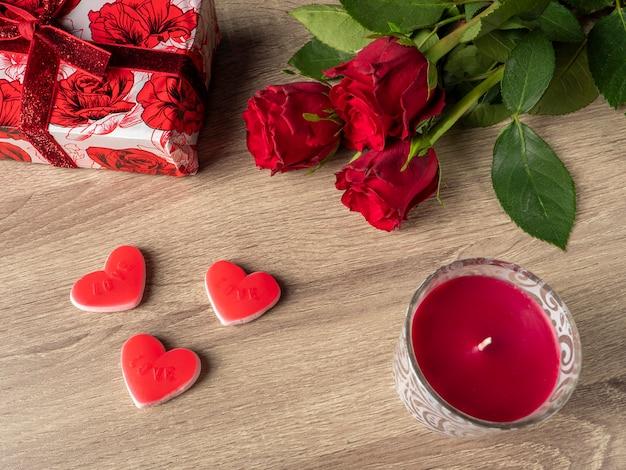 Rosas vermelhas com corações vermelhos de vela vermelha e presente vermelho na mesa