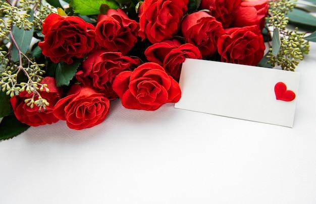 Rosas vermelhas com eucalipto em fundo branco