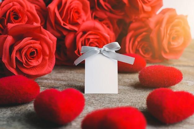 Rosas vermelhas, coração vermelho e cartão de rótulo branco em uma mesa de madeira