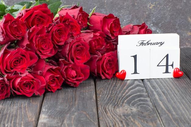 Rosas vermelhas, corações vermelhos e uma data do calendário de 14 de fevereiro