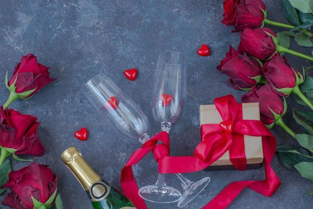 Rosas vermelhas, corações vermelhos, uma garrafa de champanhe, duas taças, um presente em uma caixa