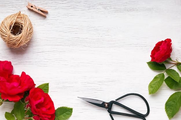 Rosas vermelhas, corda de juta e tesoura na mesa de madeira branca, vista superior