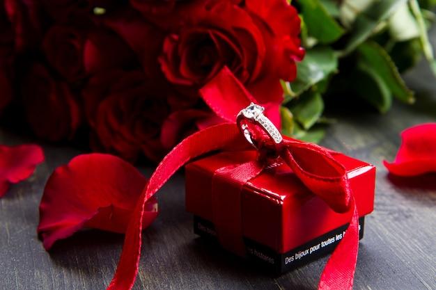 Rosas vermelhas de dia dos namorados e caixa de presente em um fundo de madeira