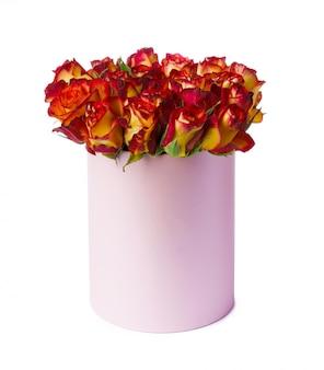 Rosas vermelhas e amarelas em uma caixa de chapéu