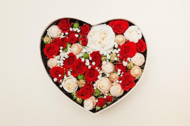Rosas vermelhas e brancas em uma caixa branca em forma de coração