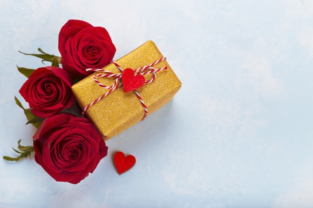 Rosas vermelhas e caixa de presente dourada