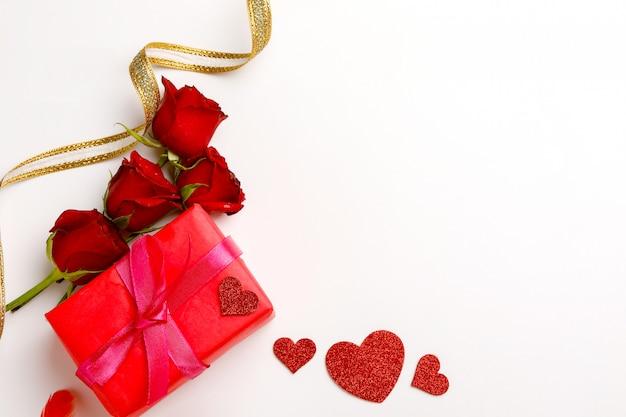 Rosas vermelhas e caixa de presente em fundo branco.