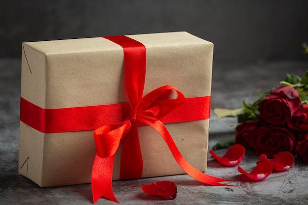 Rosas vermelhas e caixa de presente em fundo escuro