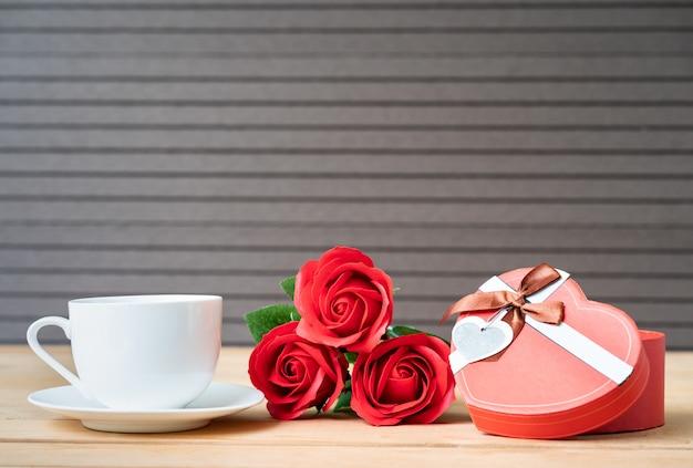 Rosas vermelhas e caixa de presente em madeira fundo