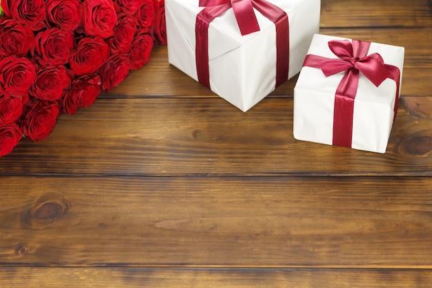 Rosas vermelhas e caixa de presente na mesa de madeira marrom