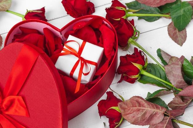 Rosas vermelhas e caixa de presente na mesa de madeira