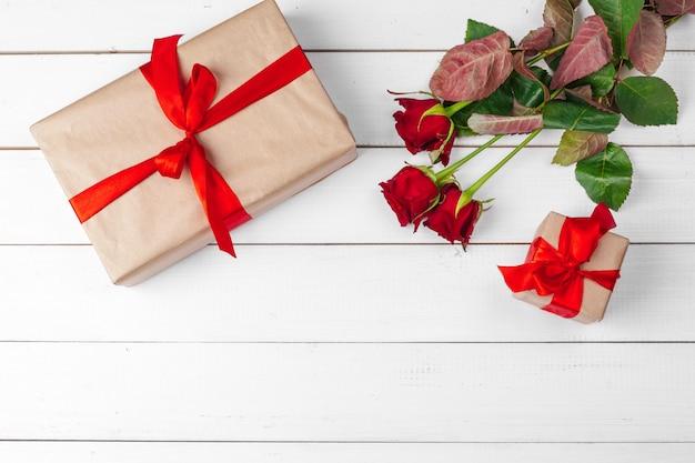 Rosas vermelhas e caixa de presente na mesa de superfície de madeira