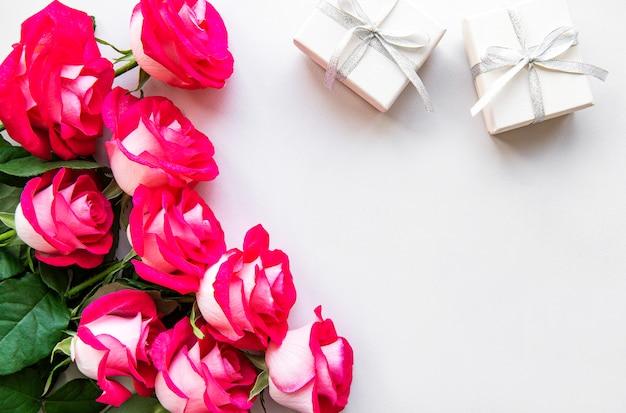 Rosas vermelhas e caixas de presente em um fundo branco