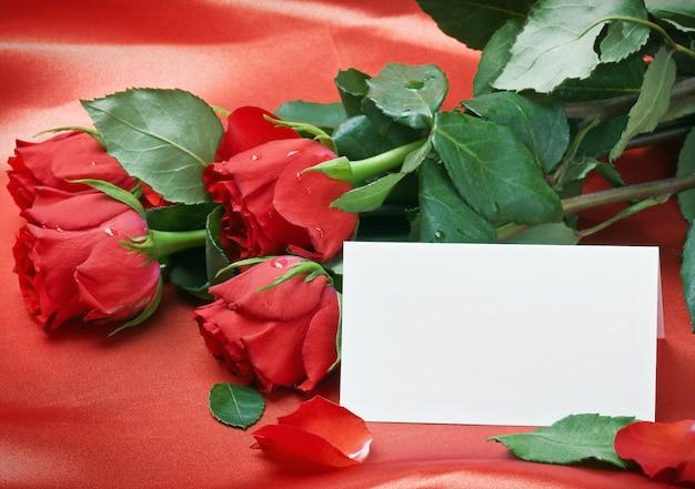 Rosas vermelhas e cartão branco com um lugar para um texto de felicitações