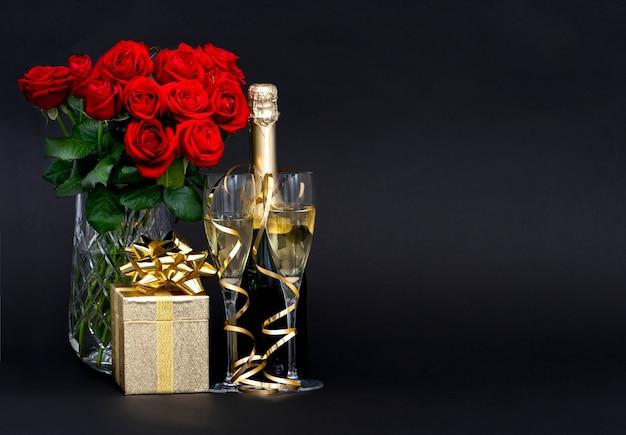 Rosas vermelhas e champanhe com decoração dourada em fundo preto
