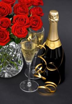 Rosas vermelhas e champanhe. decoração festiva. arranjo romântico. foco seletivo