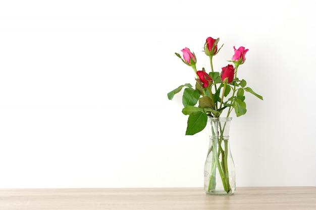 Rosas vermelhas e cor de rosa em vaso de vidro na mesa e fundo de parede branca com espaço de cópia