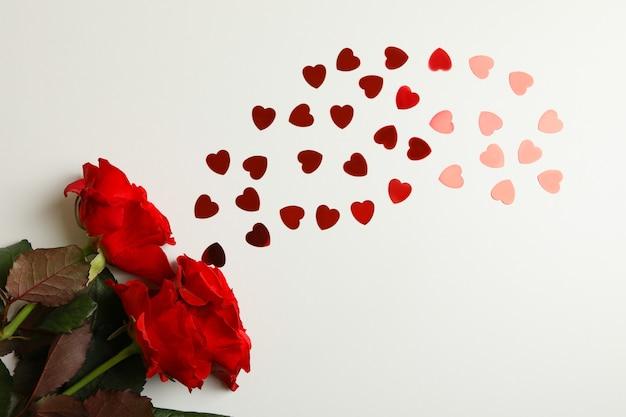 Rosas vermelhas e corações brilhantes em fundo branco