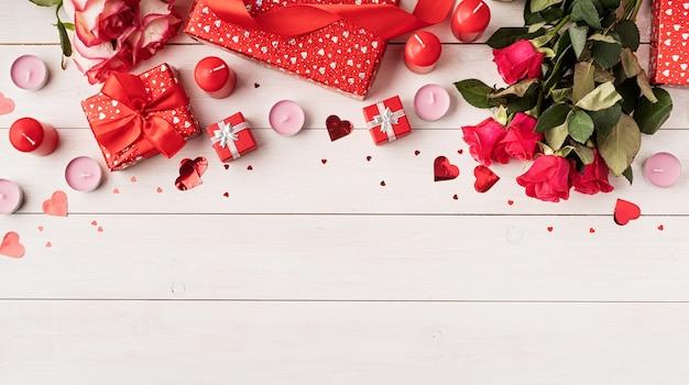 Rosas vermelhas e decoração do dia dos namorados vista superior em fundo branco de madeira