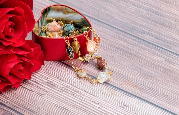 Rosas vermelhas e um recipiente de jóias em forma de coração