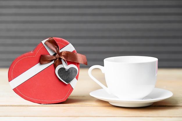 Rosas vermelhas e xícara de café sobre fundo de madeira