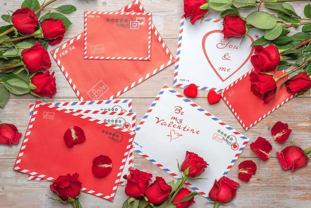 Rosas vermelhas em buquês cartas correio artesanato sacola de compras saudações fundo de selos de dia dos namorados