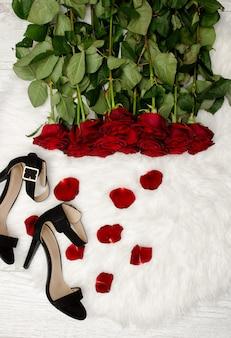 Rosas vermelhas em pêlo branco, sapatos pretos e pétalas de rosa, vista superior