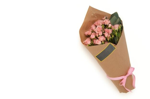Rosas vermelhas em um buquê de papel amarrado com fita adesiva em um fundo branco. dia dos namorados