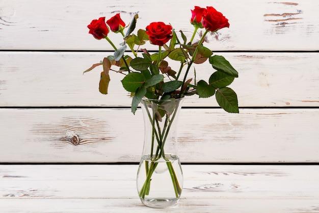 Rosas vermelhas em um vaso de vidro com flores sobre fundo de madeira claro flores delicadas para a senhora símbolo do romance