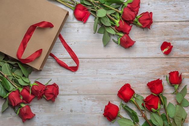 Rosas vermelhas em uma sacola de compras de artesanato em uma superfície de madeira entrega de flores no dia dos namorados, 14 de fevereiro