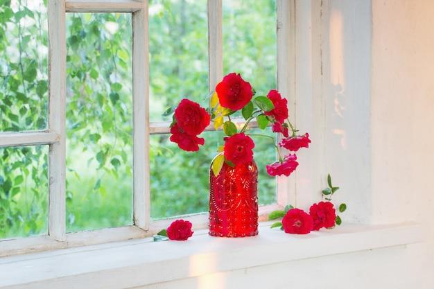 Rosas vermelhas em vaso de vidro vermelho no peitoril da janela
