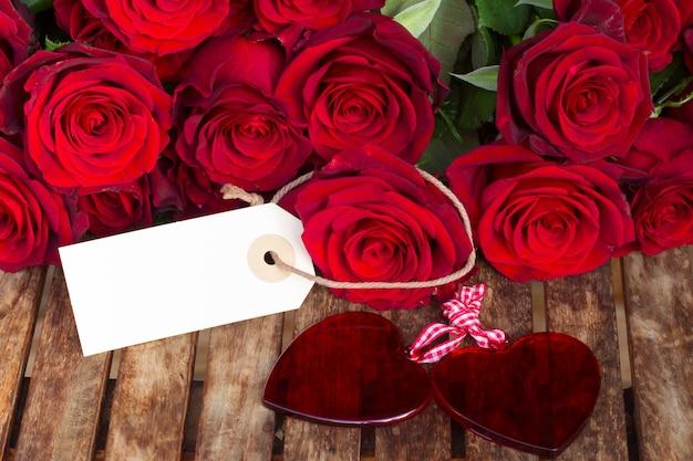 Rosas vermelhas escuras com dois corações e etiqueta na mesa de madeira