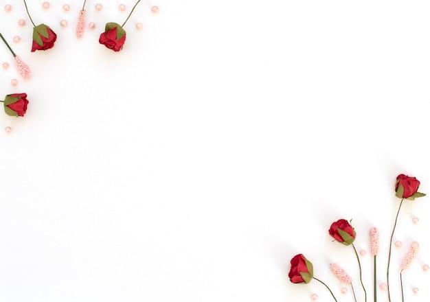 Rosas vermelhas, flores cor de rosa e miçangas em fundo branco