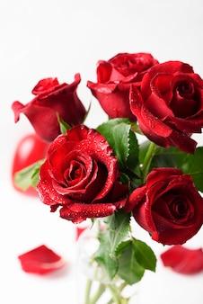 Rosas vermelhas frescas na mesa branca, foco seletivo