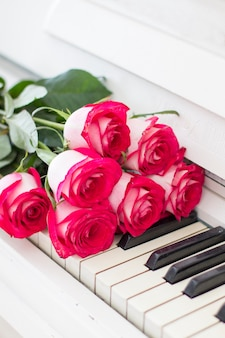 Rosas vermelhas luxuosas em um piano. buquê de rosas vermelhas e teclas de piano