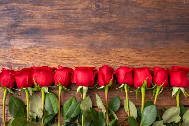 Rosas vermelhas na mesa de madeira. mesa de dia dos namorados. vista superior com espaço de cópia