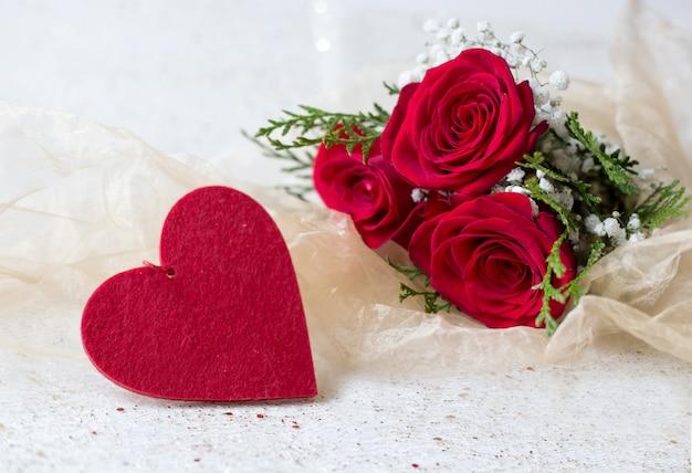 Rosas vermelhas naturais e coração de feltro com cartão de amor com fundo dourado brilhante
