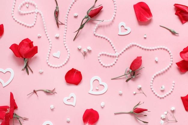 Rosas vermelhas, pétalas, corações e pérolas sobre vista superior rosa