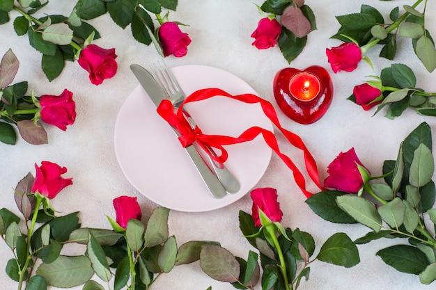 Rosas vermelhas são dispostas em círculo, um prato rosa, talheres amarrados com uma fita vermelha, um castiçal com uma vela