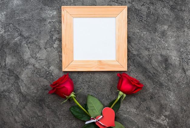 Rosas vermelhas, sinal de coração e moldura