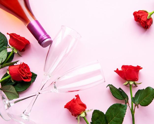Rosas vermelhas, vinho e taças para vinho em um rosa claro