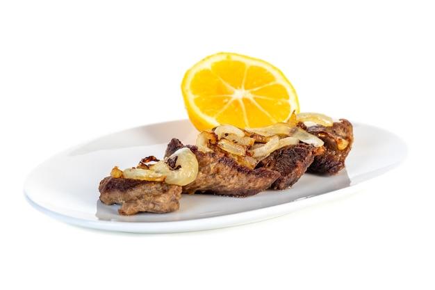 Rosbife com cebola e limão em um prato branco. comida.