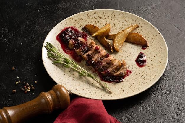Rosbife com molho de cranberry, alecrim e pêra frita. prato com prato de carne em uma mesa preta.