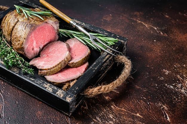 Rosbife redondo com carne em tabuleiro de madeira com ervas aromáticas. fundo escuro. vista do topo. copie o espaço.