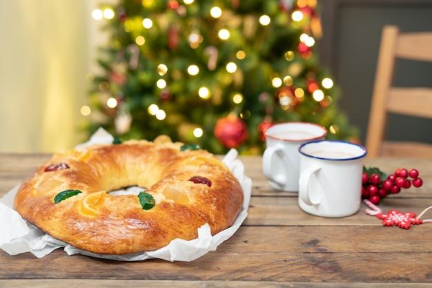 Roscón de reyes inteiro na mesa de madeira com a árvore de natal ao fundo. doces de natal.