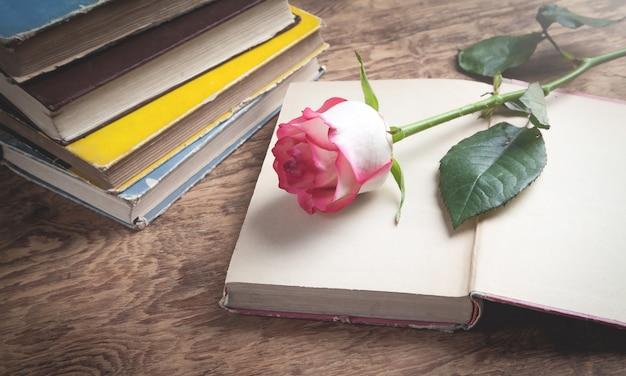 Rose e livro sobre o fundo de madeira.