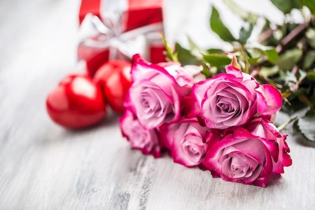 Roses. rosas cor de rosa com dois corações e presente vermelho.