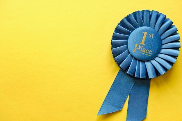 Roseta da fita azul para o primeiro vencedor colocado